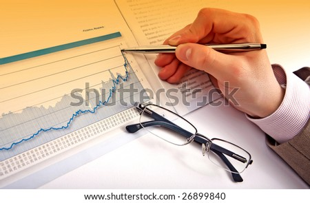 Businessman's hand showing diagram on financial report with pen. Business background 07 - stock photo