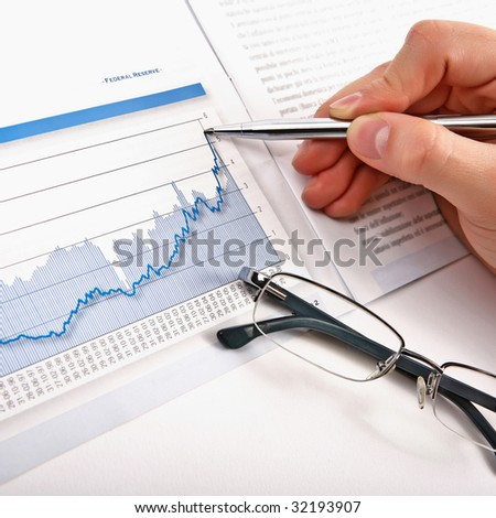 Businessman's hand showing diagram on financial report with pen. Business background 12 - stock photo