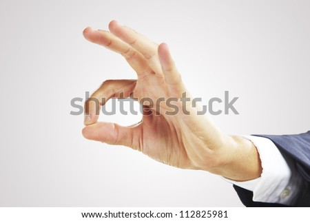 Businessman's hand showing OK sign.