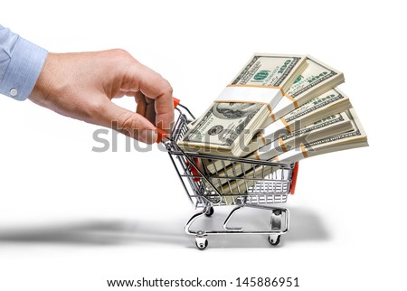 businessman's hand & steel grocery cart full of money stacks / man's hand holds grocery cart full of money stacks - isolated on white background