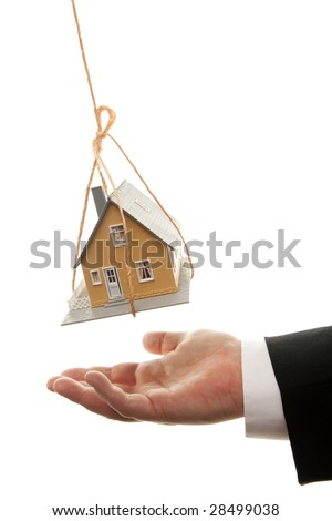 Businessman's Hand Under Dangling House Isolated on a White Background. - stock photo