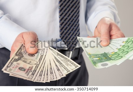 Businessman's hands giving dollar and euro banknotes to you - stock photo