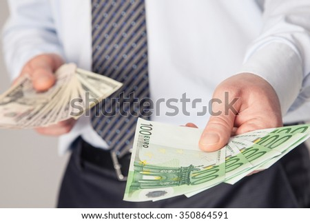 Businessman's hands giving euro and dollar banknotes to you - stock photo