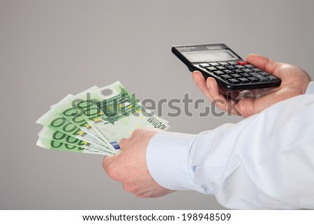 Businessman's hands holding euro banknotes and calculator on gray background - stock photo