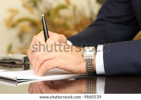 Businessman's hands on the table with reflection - stock photo