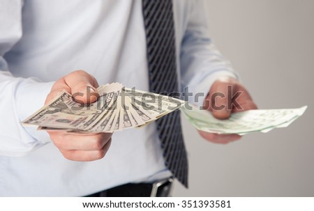 Businessman's hands proposing dollar and euro banknotes to you - stock photo