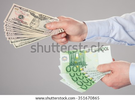 Businessman's hands reaching out dollar and euro banknotes - stock photo