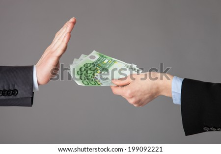 Businessman's hands rejecting an offer of money on grey background - stock photo