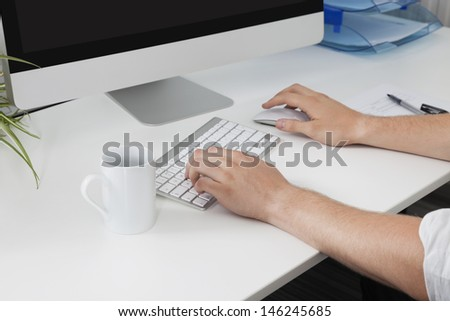 Businessman's hands using computer at desk