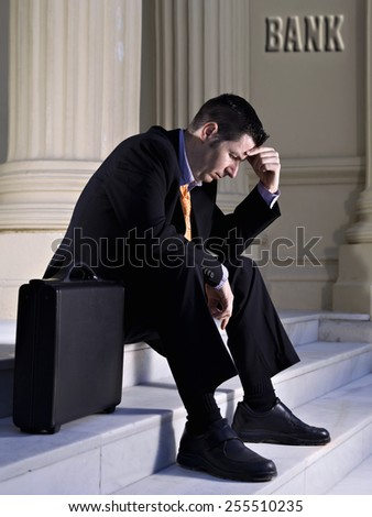 Businessman sat in a stairs looking towards to down