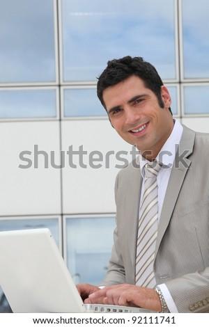 Businessman sat outside modern office block - stock photo