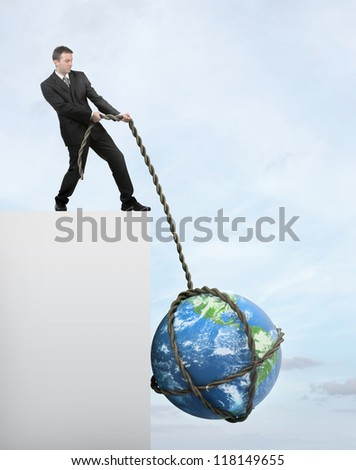 Businessman saving Earth from falling of the cliff. Elements of this image furnished by NASA