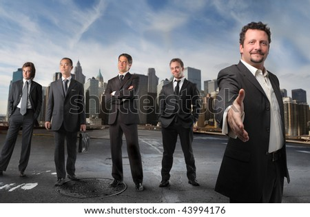 Businessman saying welcome with his team on the background - stock photo