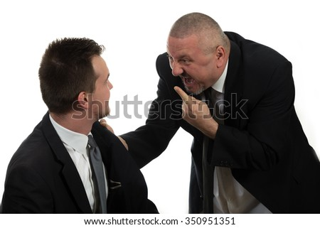 Businessman screaming and fighting at a young colleague - stock photo
