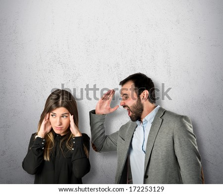 Businessman screaming at his girlfriend over grey background