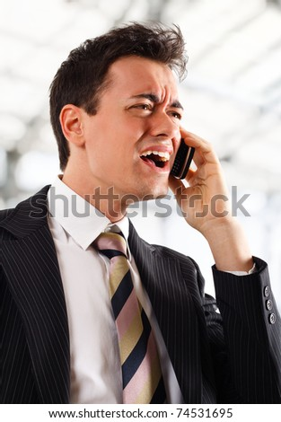Businessman screaming at the phone. Bright blurred background. - stock photo