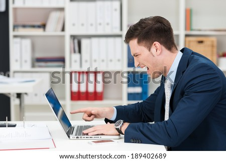 Businessman screaming in horror and pointing at his laptop as he reads something upsetting on the screen, side view in the office - stock photo