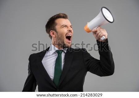 Businessman screaming in megaphone isolated on grey background. Businessman speaking loud through megaphone - stock photo