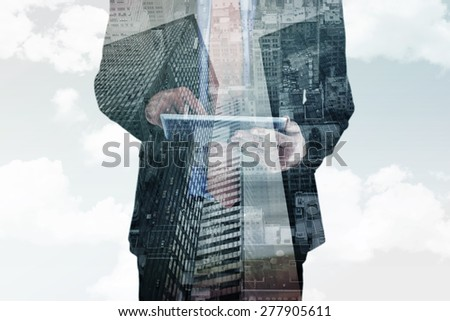 Businessman scrolling on his digital tablet against low angle view of skyscrapers - stock photo