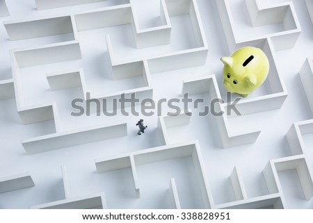Businessman searching for piggy bank hidden inside a maze - stock photo