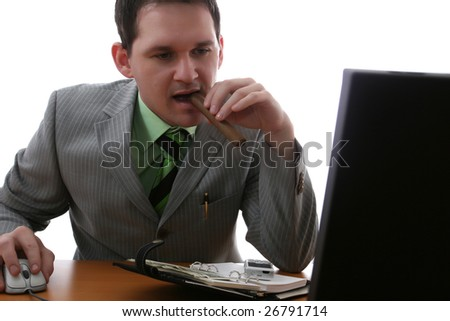 Businessman seated at desk looking at his computer and holding cigar