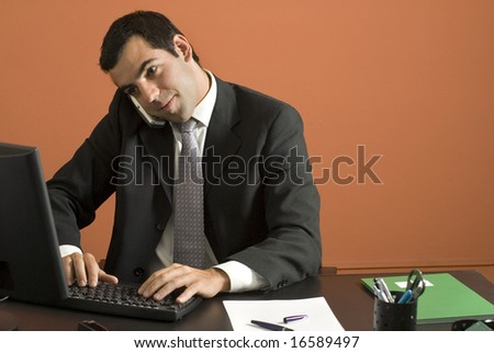 Businessman seated at desk looking at his computer while talking on his phone. Horizontally framed photo. - stock photo