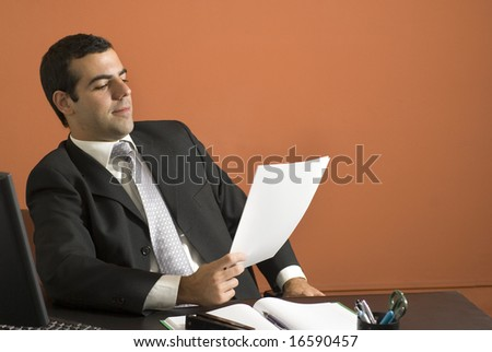 Businessman seated at desk looking at paperwork. Horizontally framed photo. - stock photo