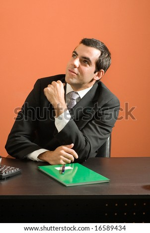 Businessman seated at desk looking at paperwork. Vertically framed photo. - stock photo