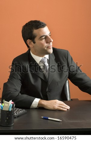 Businessman seated at desk looking off into the distance. Vertically framed photo. - stock photo