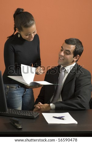 Businessman seated at desk while his co-worker shows him paperwork. Vertically framed photo. - stock photo