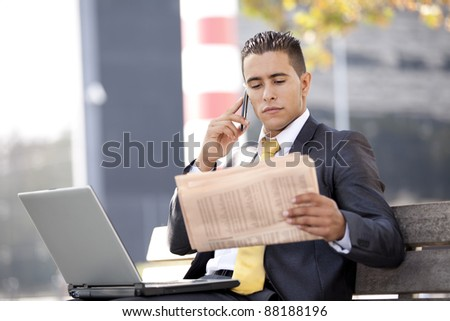 Businessman seated in a bench working with his laptop, calling at the cellular and reading his newspaper