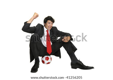 Businessman seated in a soccer ball watching the results in his cellphone isolated in white