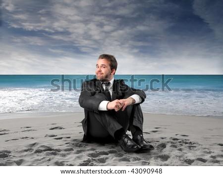 businessman seated on the beach - stock photo