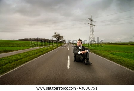 businessman seated on the street - stock photo