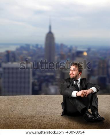 businessman seated on the top of NY building - stock photo