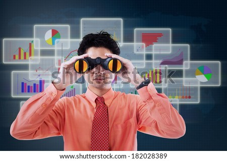 Businessman see vision using binoculars in front of business futuristic background - stock photo