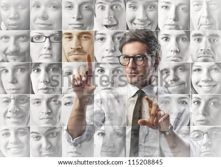 Businessman select a contact from a list with the profile images - stock photo