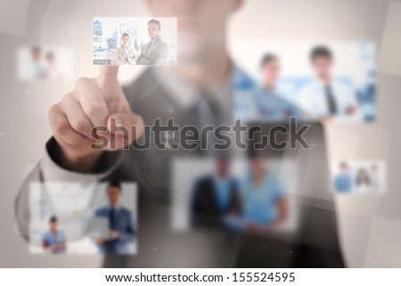 Businessman selecting a picture on blurred background - stock photo