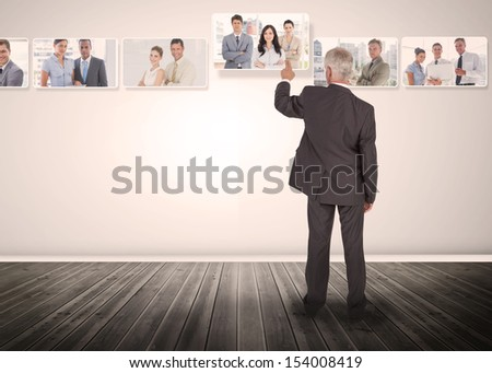 Businessman selecting business people digital interface among group of pictures - stock photo
