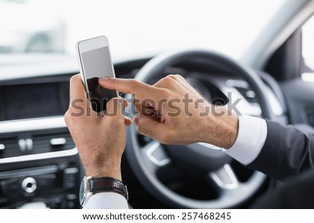 Businessman sending a text message in his car - stock photo