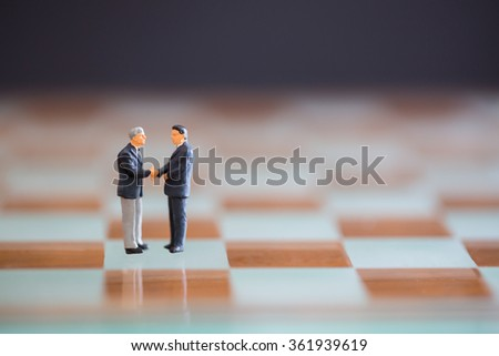 Businessman shake hands for good corporate business with chess game concept.