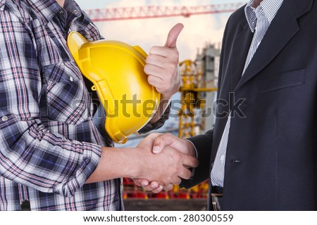 businessman shake hands with engineering construction site - stock photo