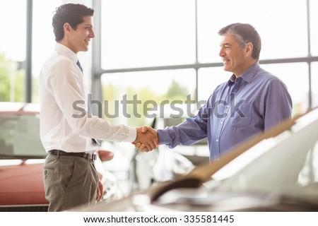 Businessman shaking a customer hand at new car showroom - stock photo