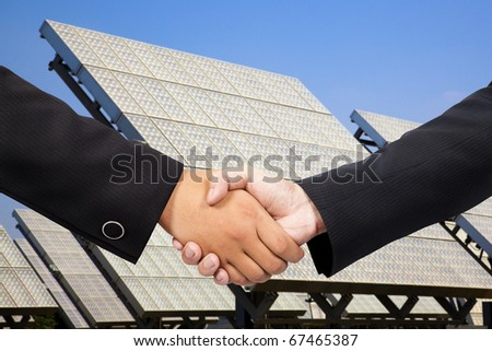 Businessman shaking hand before Solar power plant - stock photo