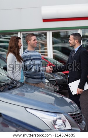 Businessman shaking hand  of a man in a dealership - stock photo