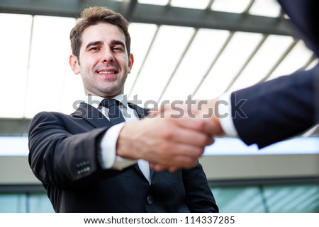 Businessman shaking hands at the office on blurred background - stock photo
