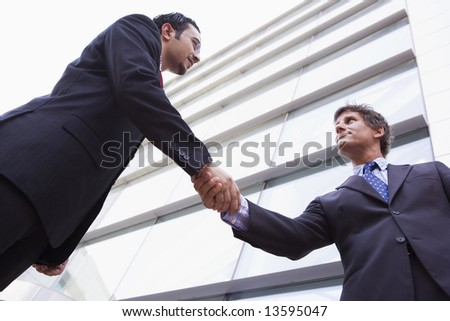 Businessman shaking hands outside modern office building - stock photo