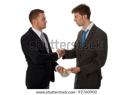 Businessman shaking hands. The deal is made and one businessman is paying the other. - stock photo