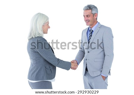 Businessman shaking hands with a businesswoman against a white wall - stock photo