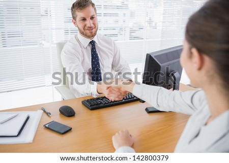 Businessman shaking hands with a colleague at his desk in the office - stock photo